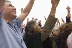 People With Raised Hands In Rally. Crowd of multiethnic people with raised hands in a rally Royalty Free Stock Photos