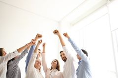 People raising fists together indoors. Unity concept royalty free stock image