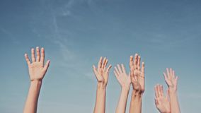 People rasing hands on blue sky background. Voting, democracy or volunteering concept.  royalty free stock photography