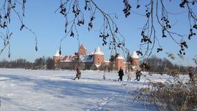 People recreate Trakai castle snow frozen lake tree twigs. People tourist recreate near ancient Trakai castle fortification covered with snow near frozen lake stock video