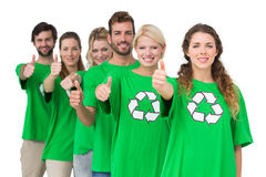 People in recycling symbol tshirts gesturing thumbs up. Group portrait of young people in recycling symbol tshirts gesturing thumbs up over white background Royalty Free Stock Image