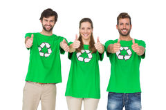 People in recycling symbol tshirts gesturing thumbs up. Portrait of young people in recycling symbol tshirts gesturing thumbs up over white background Stock Photo
