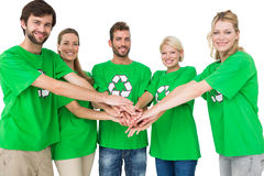 People in recycling symbol tshirts with hands together. Group portrait of young people in recycling symbol tshirts with hands together over white background Stock Images