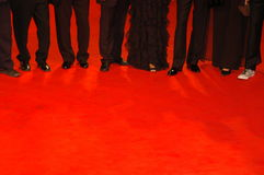 People  on red carpet. Some people standing on a  red carpet in elegant dress Stock Images