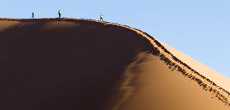People on a red dune in the Namib Desert, in Sossusvlei, Namibia Stock Image