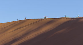 People on a red dune in the Namib Desert, in Sossusvlei, Namibia Stock Photo