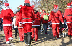 People with red Santa Claus clothes run in the public park of th Stock Image