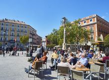 People refreshing on a terrace in the Jacinto Benavente square of Madrid, Spain royalty free stock photography