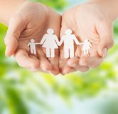 Female hands with paper family pictogram. People and relations concept - close up of female hands with paper family pictogram over green natural background Stock Photography