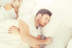 Couple sleeping in bed at home Stock Photo