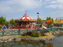 People relax in the amusement park, Sochi, Russia. Bright carousel for kids, decorative pond, green trees, people walking, Sochi Park, Russia Stock Photography