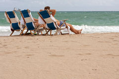 People Relax In Beach Chairs On Florida Beach. Ft. Lauderdale, FL, USA - December 28, 2013: People relax in beach chairs on the beach of a Florida resort over royalty free stock photo