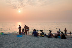 People relax on the beach at sunset Royalty Free Stock Image