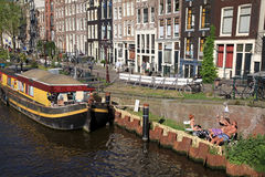 People relax on canal embankment near houseboat in Amsterdam,Net Stock Photo
