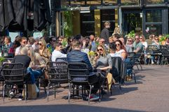 People relax and enjoy a drink. Arnhem, Netherlands - April 7, 2019: People relax and enjoy a drink at an outdoor cafe terrace at the Korenmarkt stock photography