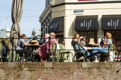 People relax and enjoy a drink. Utrecht, Netherlands - October 13, 2018: People relax and enjoy a drink at an outdoor cafe terrace stock photos