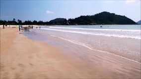 People relax and enjoy the sea on the tropical beach of Hainan Island - China stock video