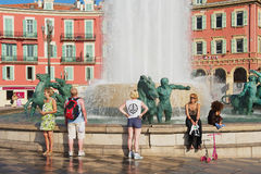 People relax at the Fontaine du Soleil at the Place Massena square on a hot day in Nice, France. Stock Photo