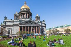 People relax on the grass in front of St. Isaac's Cathedral in St Stock Image