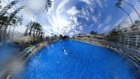 People relax at hotel swimming pool on hot day. Rabbit hole planet joyful people relax at hotel swimming pool under palm trees on hot sunny day stock video