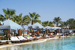 People relax by the pool with sun loungers, parasols and palm tr stock photos