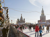 People relax on the Red Square. Moscow - November 29, 2015: Festive ice rink on Red Square, Spasskaya Tower with a clock and a lot of happy people skate at the Royalty Free Stock Images