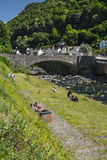 People relax by the river in the village of Lynmouth. Stock Photography