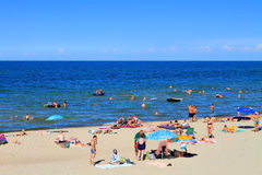 People relax on the sandy beach of the Baltic Sea in the Kulikovo. KULIKOVO, RUSSIA — JULY 19, 2014: People relax on the sandy beach of the Baltic Sea in the Stock Images