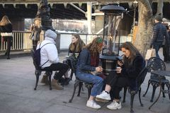 People relax in street cafes on the south bank of the Thames during Christmas markets. LONDON, UK - December 22, 2018 People relax in street cafes on the south stock image