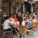 Friends relax at a cosy terrace in London Court, Perth, Australia Royalty Free Stock Images