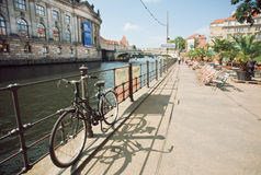 People relax on waterfront with comfortable chairs and bicycles Royalty Free Stock Photography