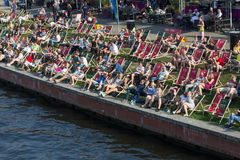 People relaxing in beach chairs at riverside Stock Images
