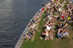 People relaxing in beach chairs at riverside Royalty Free Stock Photos