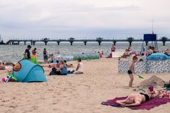 People relaxing on the beach lying on the sand and on their towels/blankets, sunbathing and enjoying the sun at the peaceful Balti stock images