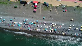 Aerial view of people relaxing on the vacation, Batumi. People relaxing on the beach during summer holidays on the beach. Aerial bird eye view of tourists on stock video footage