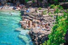 People relaxing at beautiful inviting Bruce peninsula rocky beach Royalty Free Stock Photos