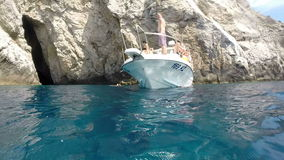 People relaxing on boat, Bisevo island, Croatia. BISEVO, CROATIA - 18 AUGUST 2015: People relaxing on boat after swimming in front of Blue cave. The cave is only stock footage