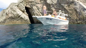People relaxing on boat, Bisevo island, Croatia. BISEVO, CROATIA - 18 AUGUST 2015: People relaxing on boat after swimming in front of Blue cave. The cave is only stock video footage