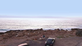 People are relaxing on the coast of the ocean after the traveling on luxury cars stock footage