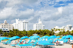 People relaxing on deck chairs under blue umbrellas Stock Photo