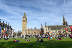 People relaxing at the Houses of Parliament. Crowd of people relaxing at the Houses of Parliament, London lounging on the green lawns in front of the Big Ben Stock Photography