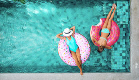 People relaxing on inflatable ring in pool. Two people mom and child relaxing on donut lilo in the pool at private villa. Summer holiday idyllic. High view from Royalty Free Stock Photography