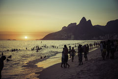 People relaxing on Ipanema Beach during beautiful summer sunset. Royalty Free Stock Images