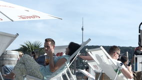 People Relaxing on Lounge Chairs, and Stuttgart Tv Tower. People relaxing and enjoying refreshing drinks while lounging. The Stuttgart tv tower  stands atop the stock video footage