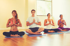 People Relaxing and Meditating in Yoga Class. Stock Photo