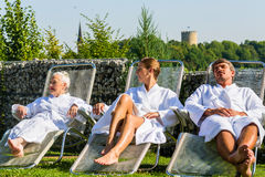People relaxing on outdoor rest area of sauna Royalty Free Stock Photo