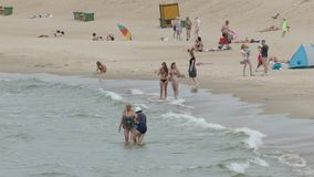 People relaxing in Palanga Beach. PALANGA, LITHUANIA - June 28, 2016: Unidentified People relaxing, sunbathing and swimming at Palanga city Beach during hot stock video footage