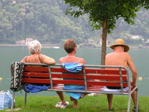 People relaxing on park bench Stock Photo
