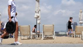 People relaxing on recliners at sandy beach, skyscrapers on horizon. People tourists relaxing on recliners at sandy beach under blue sky, skyscrapers on horizon stock video