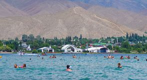 People relaxing during summer holiday in Kyrgyzstan. People swimming and relaxing during summer holiday near Cholpon-Ata, Kyrgyzstan 30.07.2017 stock photo